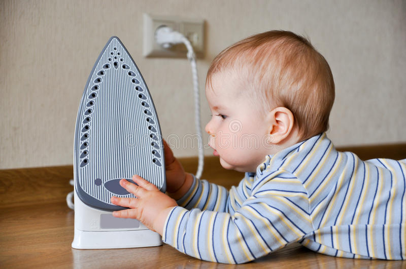 Baby touching hot iron. Unatetneded baby laying on floor and touching hot iron stock photo
