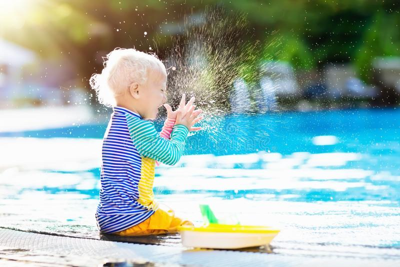 Baby in swimming pool. Family summer vacation. Baby with toy boat in swimming pool. Little boy learning to swim in outdoor pool of tropical resort. Swimming stock photography