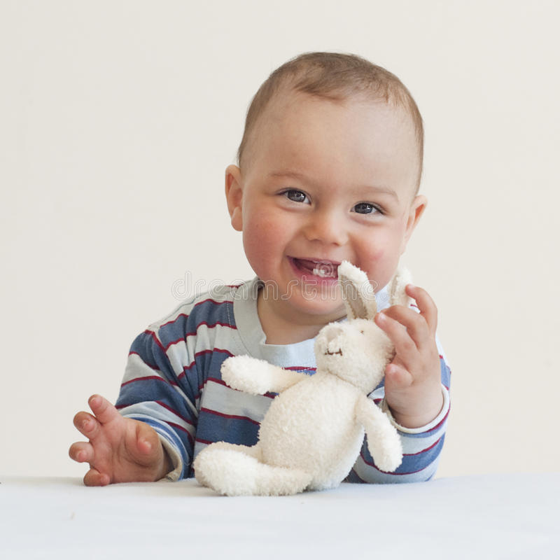 Baby with a toy rabbit. Portrait of a cute happy smiling 9 month old baby playing with of soft toy rabbit royalty free stock photos