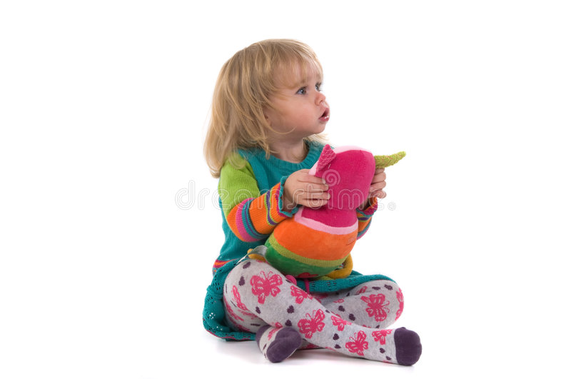 Baby with toy sitting on the floor royalty free stock photo