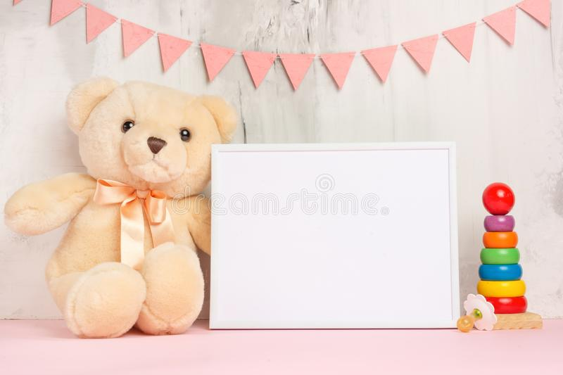Baby toys and frame on light wall background, for design. Baby shower royalty free stock photography