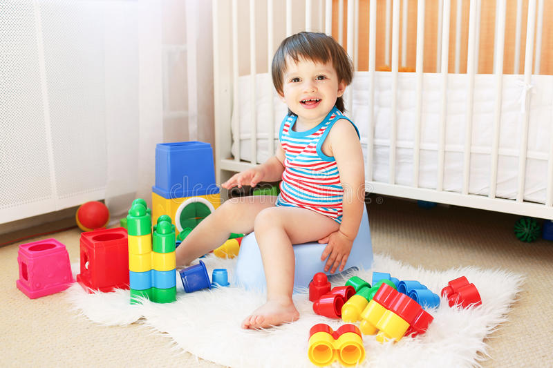 Baby with toys sitting on potty. Lovely baby with toys sitting on potty stock photography