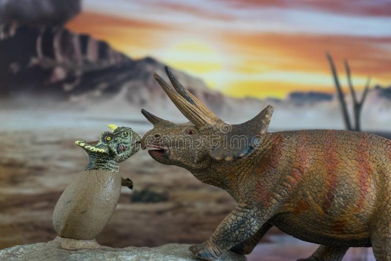 Baby triceratops into egg with triceratops mother with cretaceous land in the background. Triceratops with baby triceratops in foreground with cretaceous land in stock photos