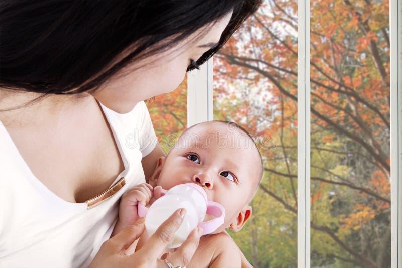 Baby trinkt Milch mit Mutter stockbilder