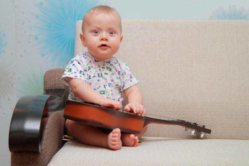Baby try to play guitar on couch royalty free stock photo