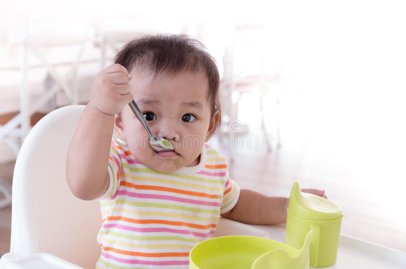 Baby tryed to eating by self royalty free stock photography