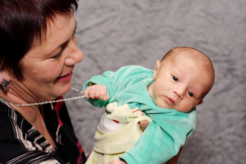 Download Baby Trying To Steal Grandmothers Necklace Stock Photo - Image: 11295838