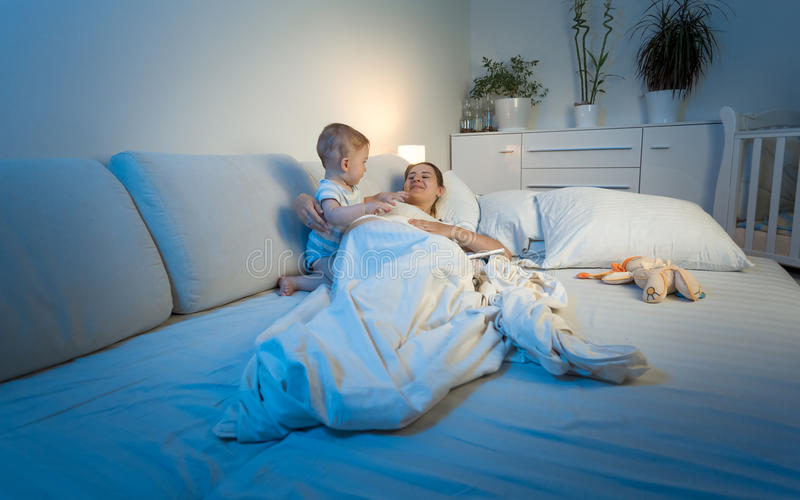 Baby trying to wake tired mother sleeping in bed. Adorable baby trying to wake tired mother sleeping in bed stock photography