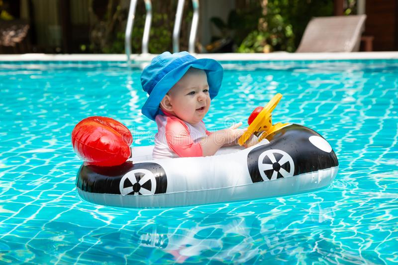 Baby turns the steering wheel. Summer vacation at sea. A little girl less than one year old is driving an inflatable boat in the royalty free stock images