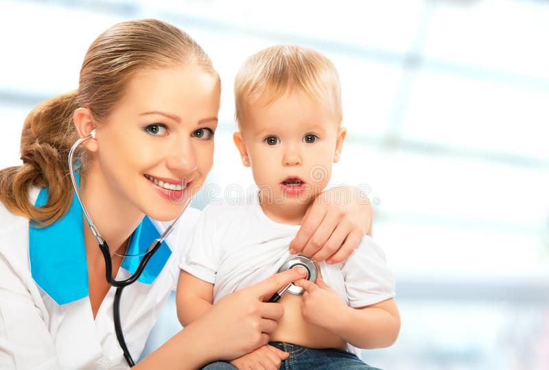 Baby und Doktorkinderarzt. Doktor hört auf das Herz mit s stockfotografie
