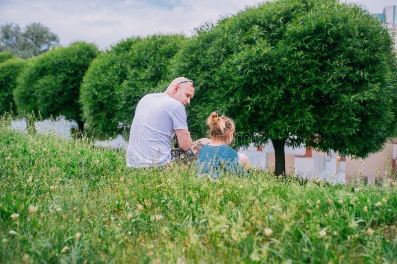 Baby und ihr Vater, die im Park sitzen R?ckseitige Ansicht lizenzfreie stockbilder