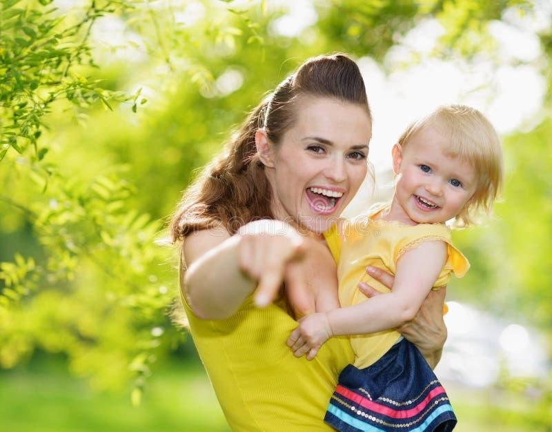 Baby und lächelnde Mutter, die in Kamera zeigen stockfotos