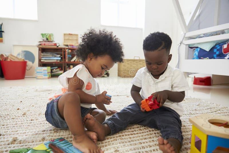 Baby und Mädchen, die zusammen mit Spielwaren im Spielzimmer spielen lizenzfreies stockbild