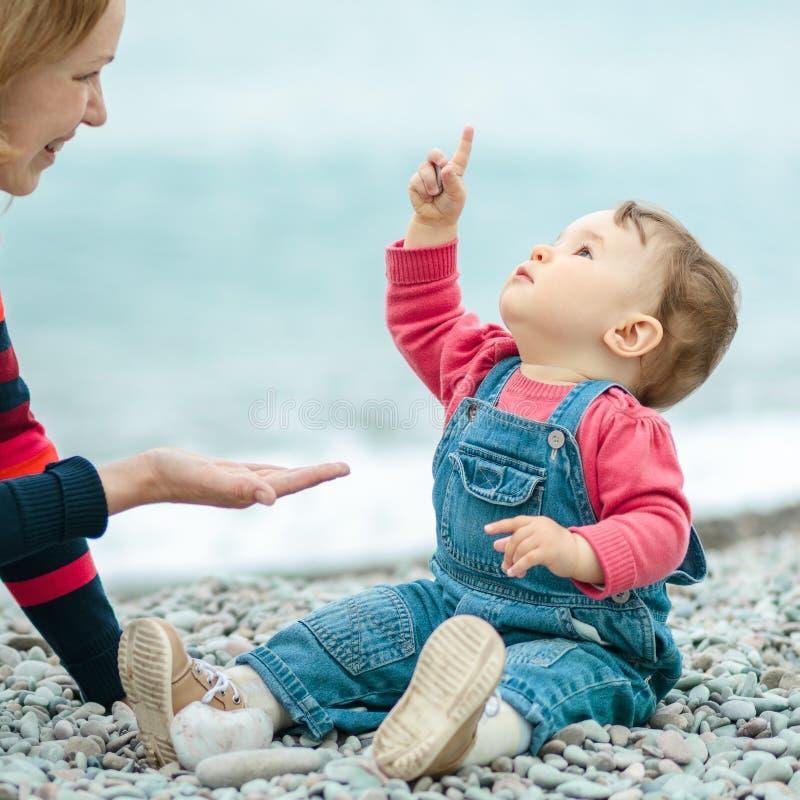 Baby und Mutter, die mit Kieseln auf dem Strand spielen lizenzfreies stockfoto