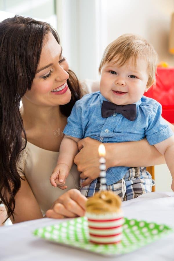 Baby und Mutter mit Geburtstags-Kuchen auf Tabelle lizenzfreies stockfoto