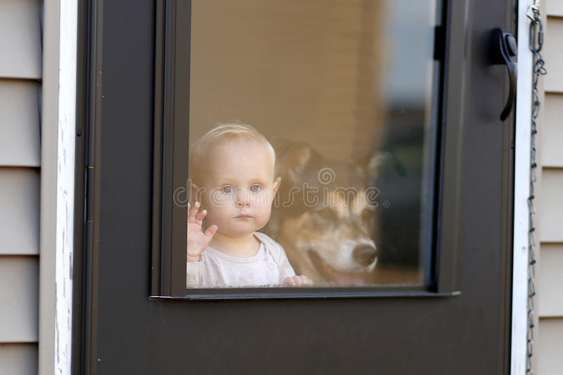Baby und Schoßhund, die an der Tür heraus schaut Fenster wartet stockbild