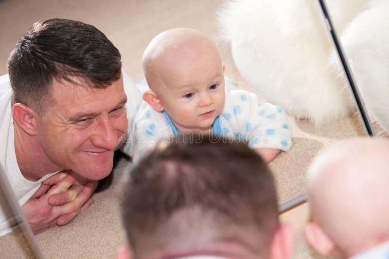 Baby und Vati, die im Spiegel schauen lizenzfreie stockfotos