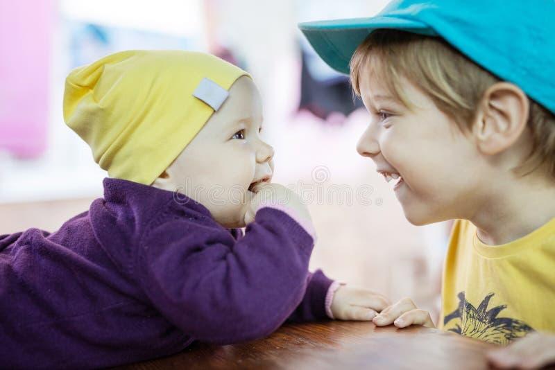 Baby und Vorschuljunge, die einander und das Lachen betrachten lizenzfreie stockfotos