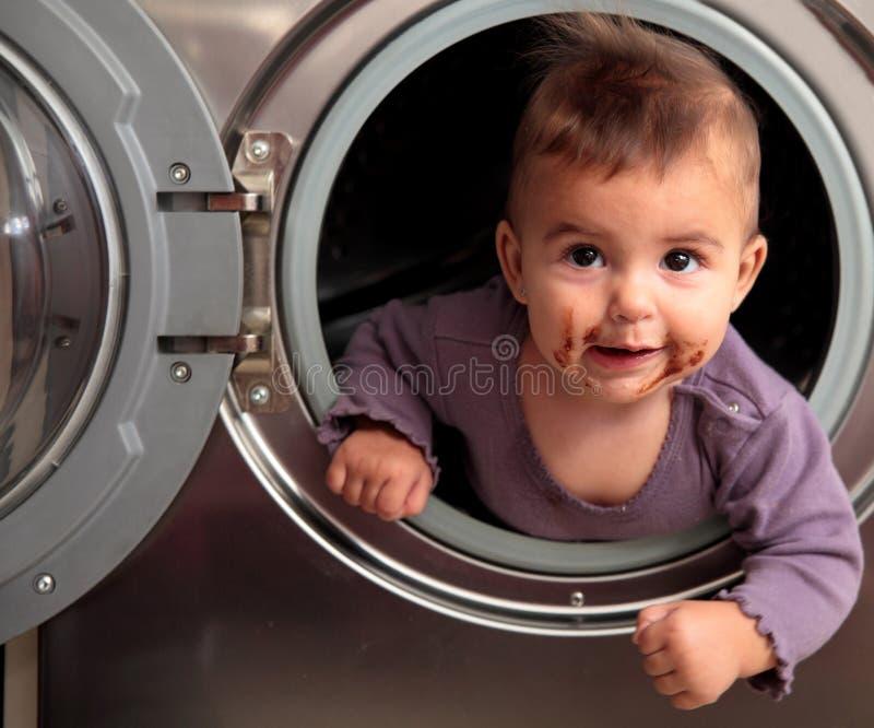 Baby und Waschmaschine stockbilder