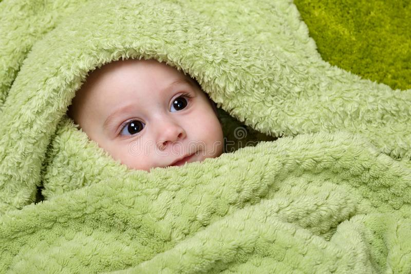 Baby unter dem grünen Tuch lizenzfreies stockfoto