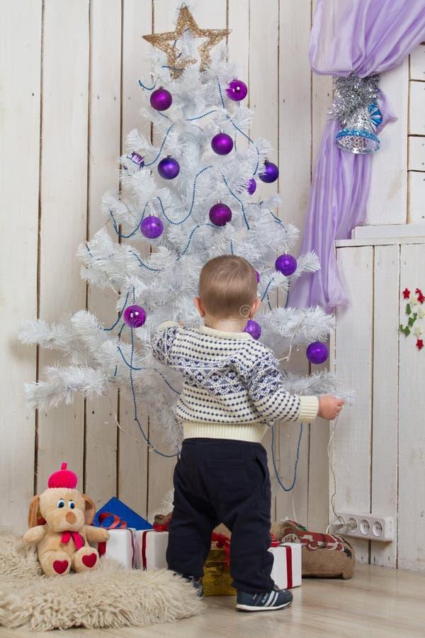 Baby unter Weihnachtstannenbaum lizenzfreie stockbilder
