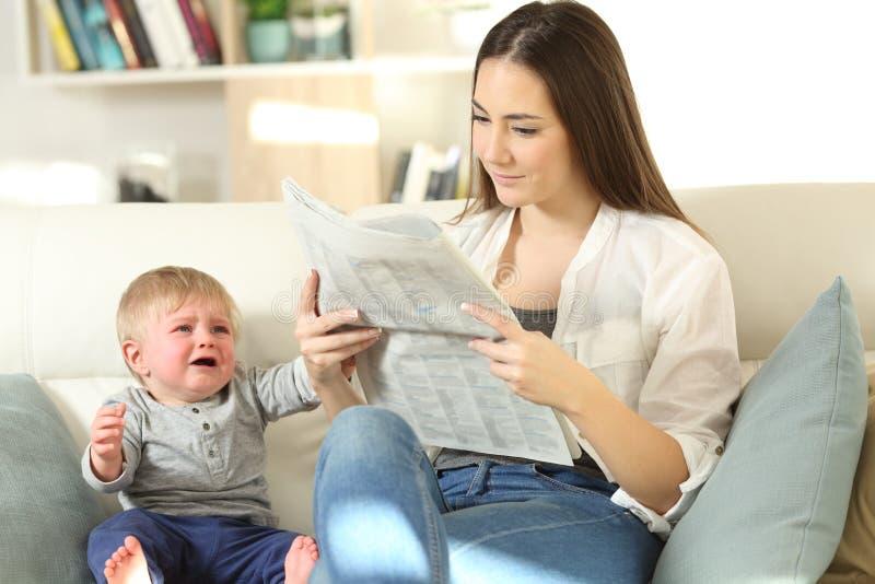 Baby veeleisende aandacht en moeder die hem negeren stock afbeeldingen