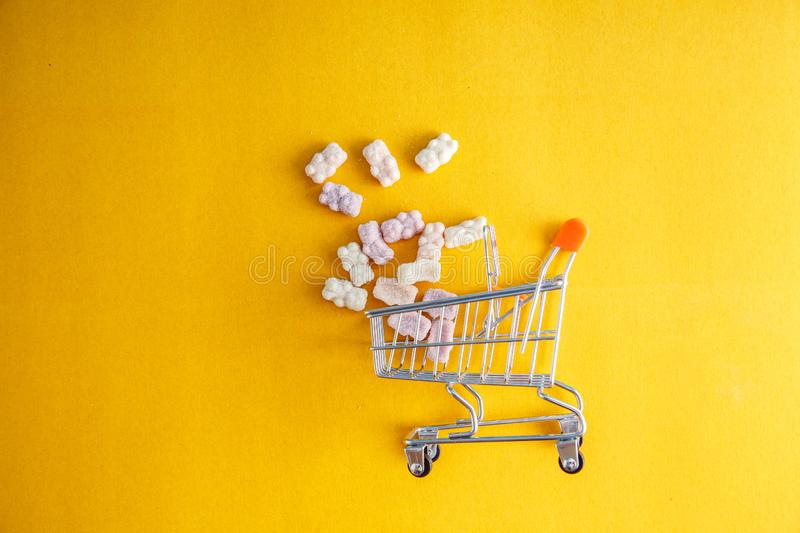 Baby vitamins in the form of bears fell out of the toy carts for products. On a bright yellow background. Pharmaceutical concept stock photography