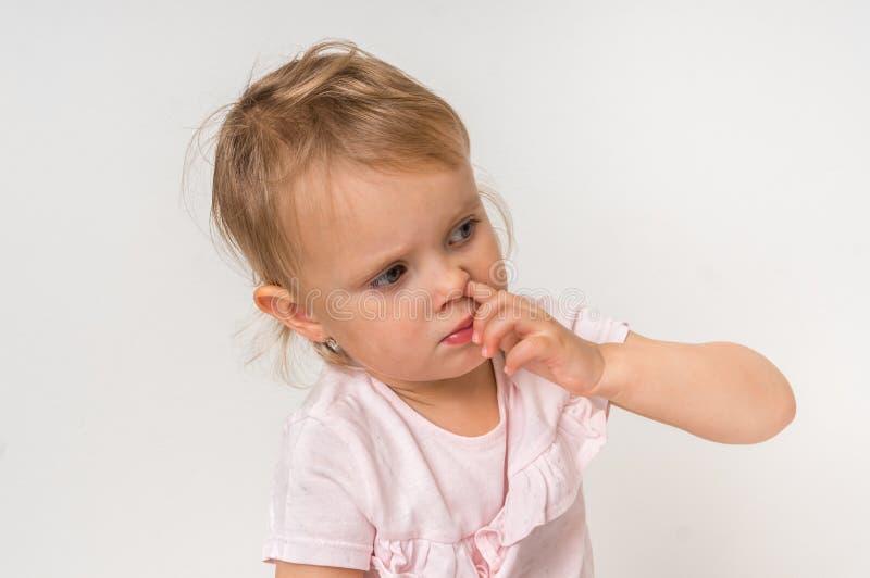 Baby wählt ihre Nase mit dem Finger nach innen aus stockfotografie