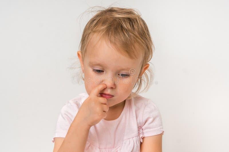Baby wählt ihre Nase mit dem Finger nach innen aus lizenzfreie stockbilder