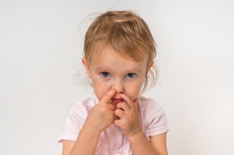 Baby wählt ihre Nase mit dem Finger nach innen aus stockbild