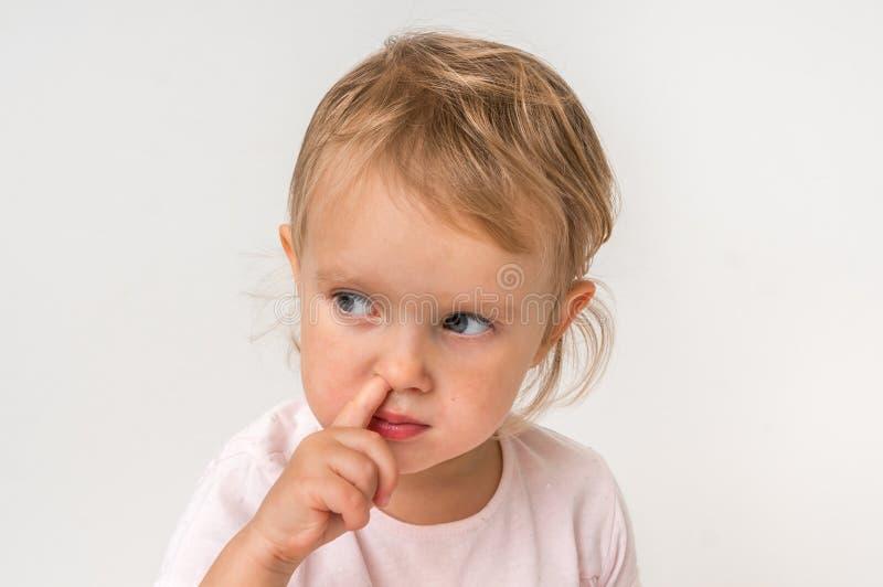 Baby wählt ihre Nase mit dem Finger nach innen aus lizenzfreies stockfoto