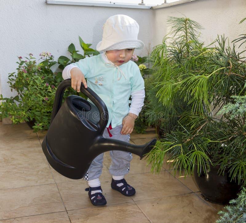 Baby wässert Blumen auf einer Terrasse mit einem großen wa lizenzfreie stockfotografie