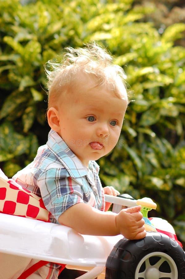 Baby walker. Baby having fun in his baby walker car royalty free stock image