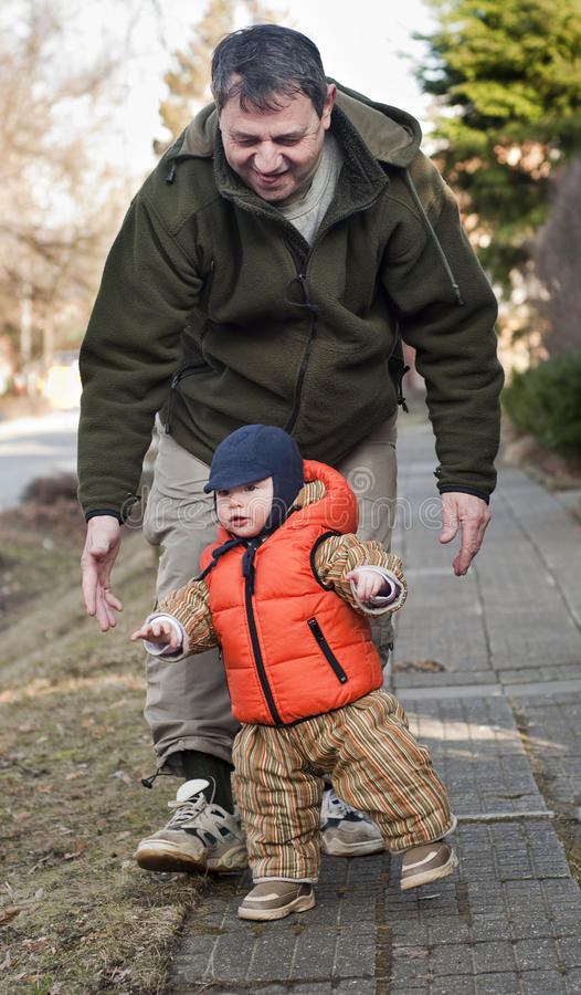 Baby walking with grandfather royalty free stock image