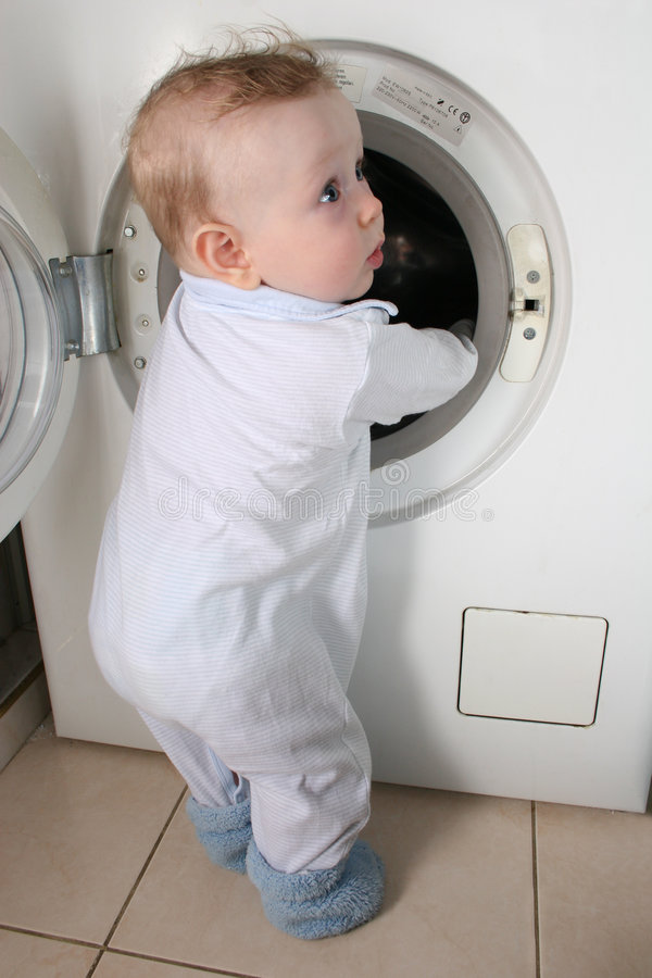 Baby with washer. Baby stand with open washer stock photo