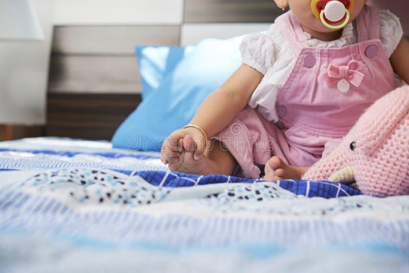 Baby wat betreft haar voeten stock afbeeldingen