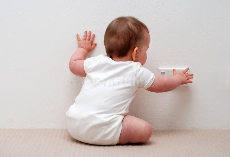 Baby wat betreft machtscontactdoos stock fotografie
