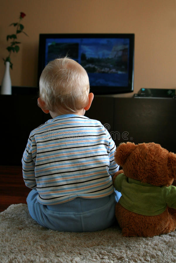 Baby watching TV royalty free stock photography