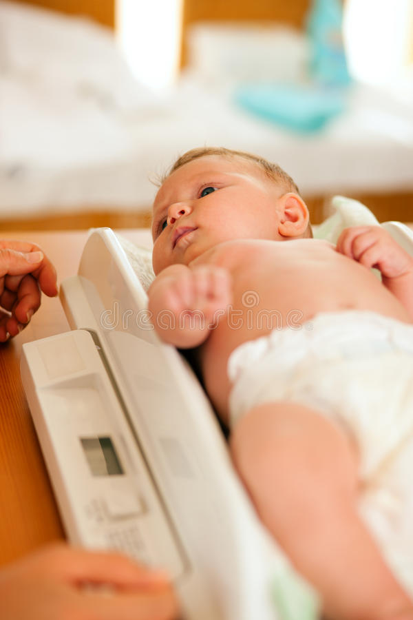 Baby on weight scale royalty free stock images