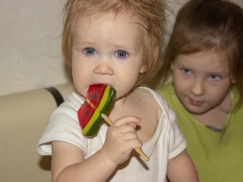 Baby in white clothes is tasting candy, a lollipop. A little disheveled blue-eyed baby in white clothes is tasting candy, a lollipop in the shape of a triangular stock photo