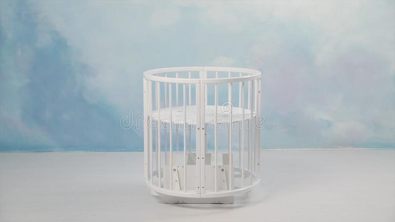 Baby white cradle swinging in the empty room in front of a wall coloured in light blue. Stock. White small baby bed stock photos