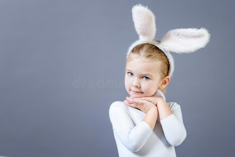 Baby in a white rabbit costume on a gray background. Cute little girl with ears of a hare, near copy space. stock photo