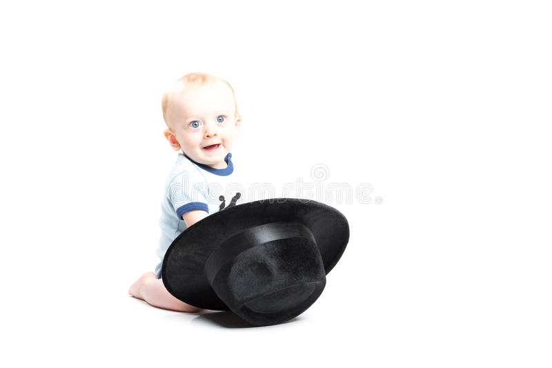 Baby on White Reaching into a Black Hat. A 6 month old baby reaches into a black fedora hat while looking at the camera royalty free stock photos