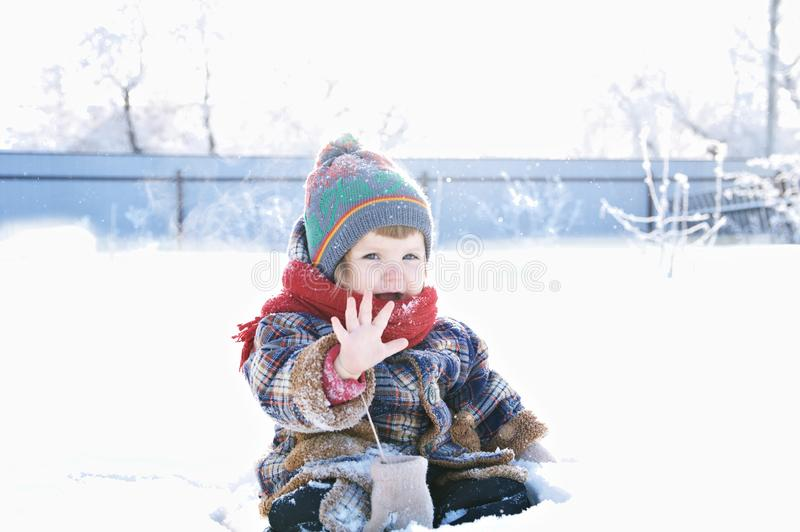 Baby in winter clothes outdoor remove her mittens and say hello. cute child in cap,scarf and mittens stock image
