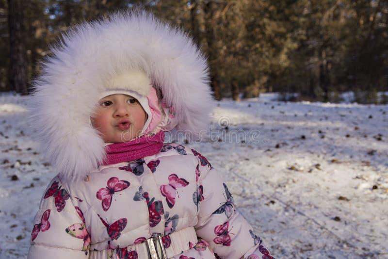 Baby am Winter Durchbrennenschnee der jungen, schönen Frau in Richtung zur Kamera auf Winterhintergrund lizenzfreies stockfoto