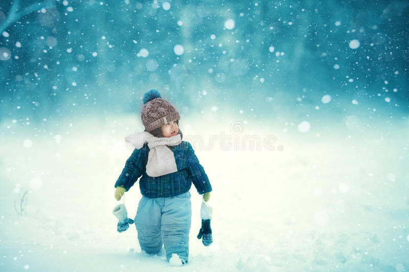 Baby in winter in the snow. The kid walks in the snow in winter in the white scarf stock images