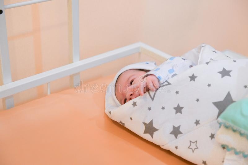 Baby wrapped in a blanket. Sleeping Cute Newborn Infant Wrapped in Baby Blanket in Acrylic Hospital Bassinet just after Birth.  royalty free stock photos