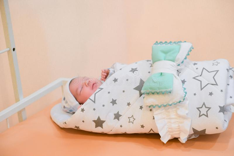 Baby wrapped in a blanket. Sleeping Cute Newborn Infant Wrapped in Baby Blanket in Acrylic Hospital Bassinet just after Birth.  stock photography