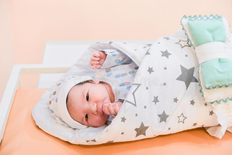 Baby wrapped in a blanket. Sleeping Cute Newborn Infant Wrapped in Baby Blanket in Acrylic Hospital Bassinet just after Birth.  royalty free stock images