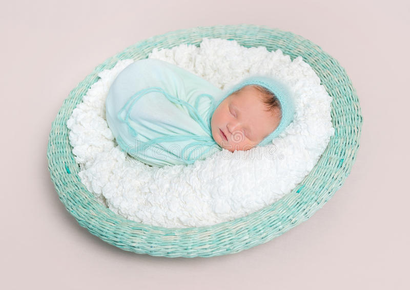 Baby wrapped in blue blanket in basket, topview stock photography